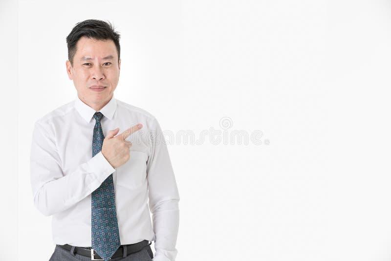 Asiatisk affärsman i den tillfälliga skjortan som som bort pekar fingret och arkivfoton