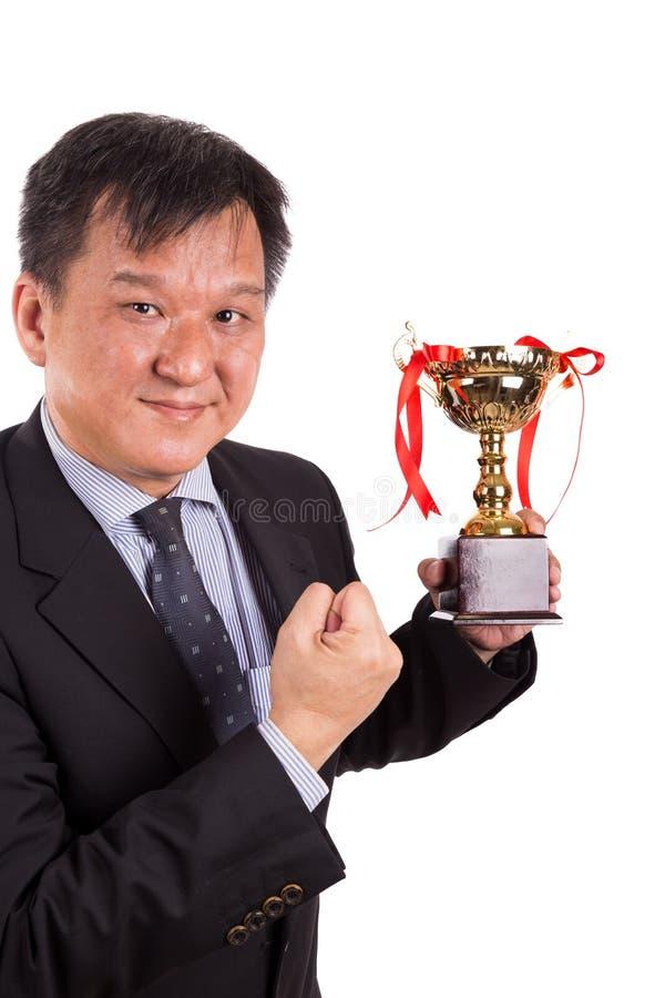 Asiatisk affärsman i dräkten som rymmer den guld- trofén fotografering för bildbyråer