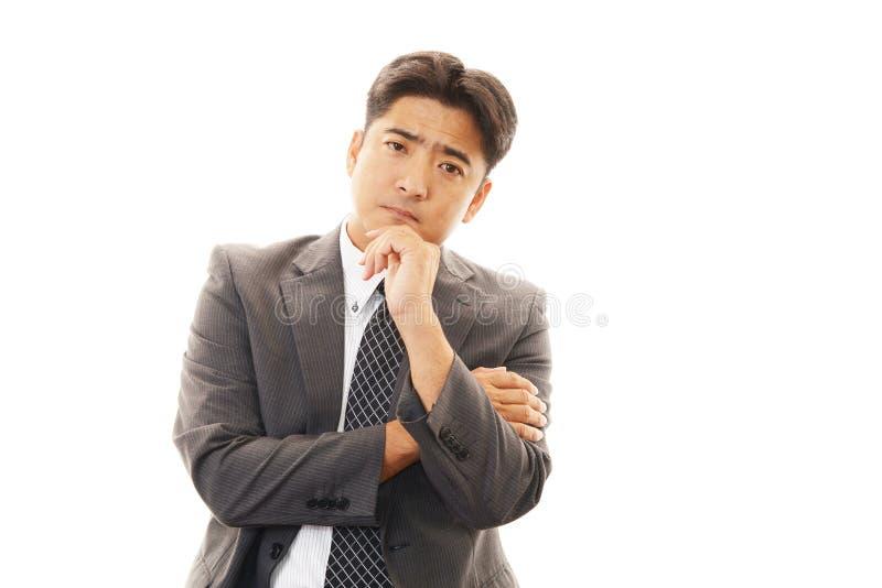 Asiatisk affärsman i en orolig blick royaltyfri bild