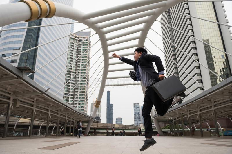 Asiatisk affärsman i formell brådska för dräktinnehavpåse i modern stad I rusa och hoppa på himmel går av stads- stad Affär i arkivfoton