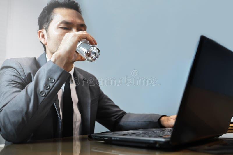 Asiatisk affärsman i grå färgdräktdricksvatten Mananvända och loo royaltyfri foto