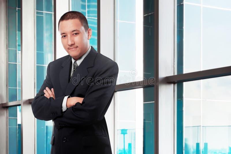 Asiatisk affärsman med armar korsat anseende i regeringsställning royaltyfria bilder