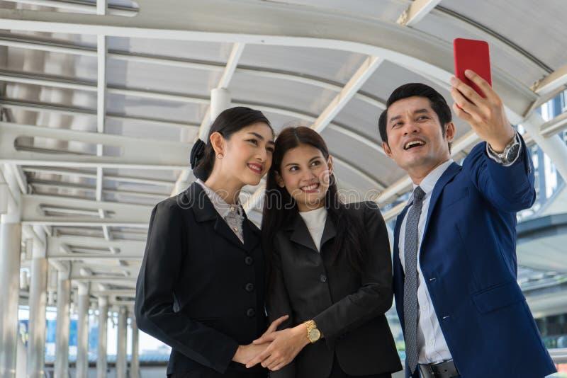 Asiatisk affärsman och affärskvinna som gör VIDEO-samtal med en vän på mobiltelefon, konceptet med konferenssamtal, facetime royaltyfri fotografi