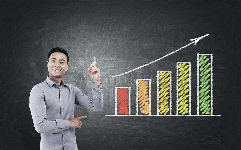 Asiatisk affärsman och en växande graf fotografering för bildbyråer