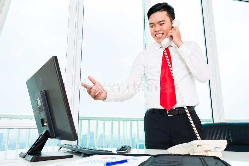 Asiatisk affärsman på telefonen som i regeringsställning arbetar arkivbild
