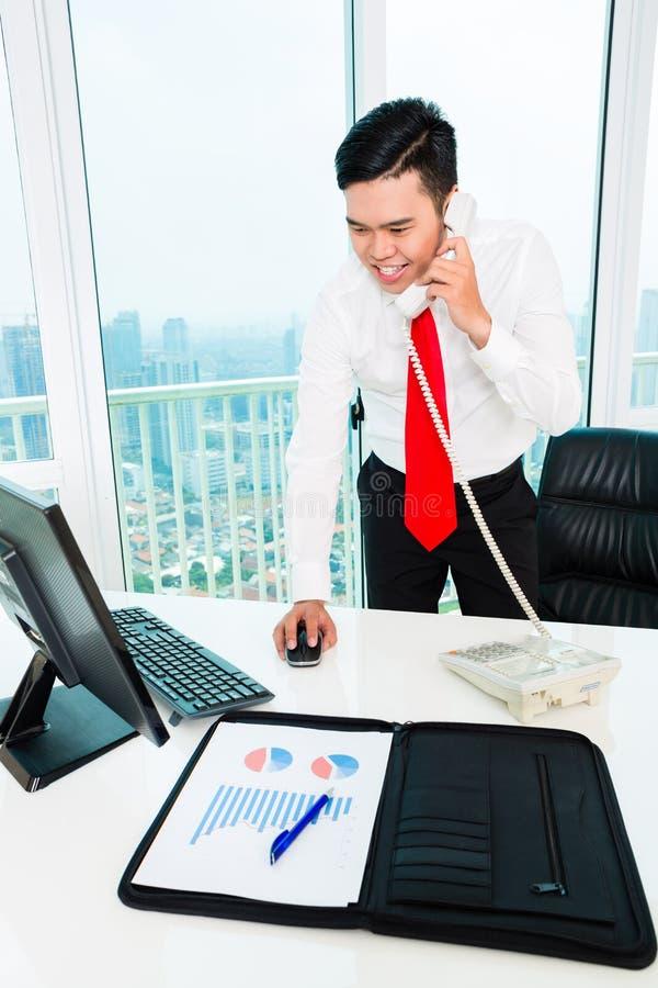 Asiatisk affärsman på telefonen som i regeringsställning arbetar royaltyfri foto
