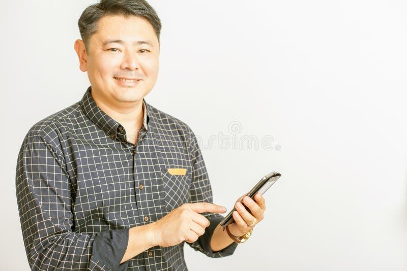 Asiatisk affärsman som använder en minnestavlaPC på vit bakgrund royaltyfri bild