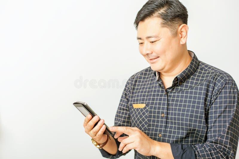 Asiatisk affärsman som använder en mobiltelefon på vit bakgrund royaltyfri bild
