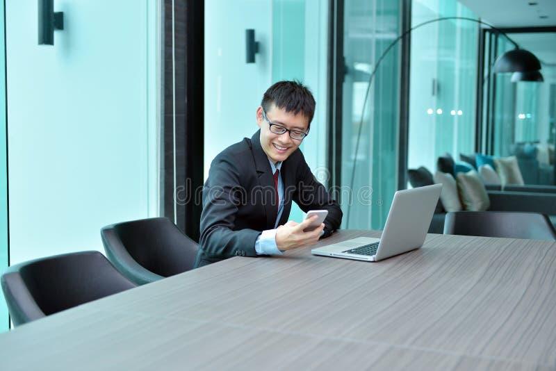 Asiatisk affärsman som använder smartphonen i ett konferensrum royaltyfria bilder