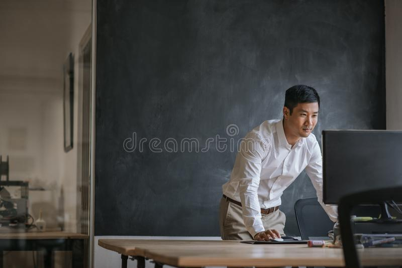 Asiatisk affärsman som arbetar på hans dator i ett kontor arkivbild