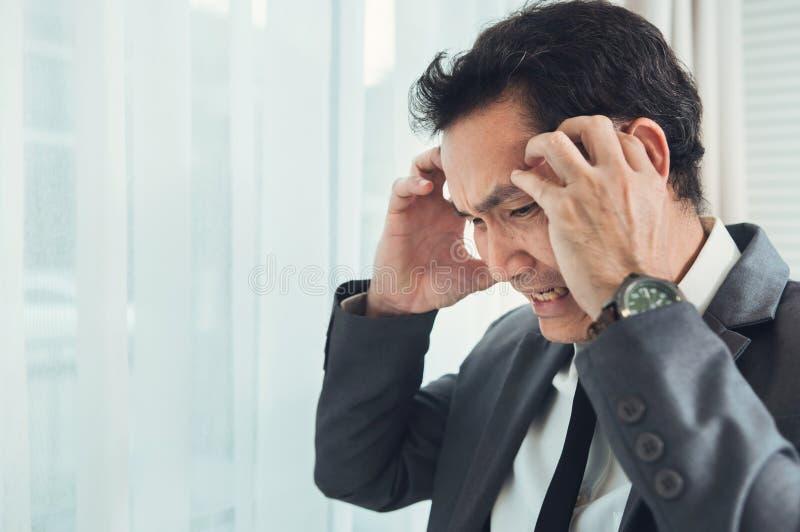 Asiatisk affärsman som har huvudvärk från migrän från överansträngt Il arkivfoton