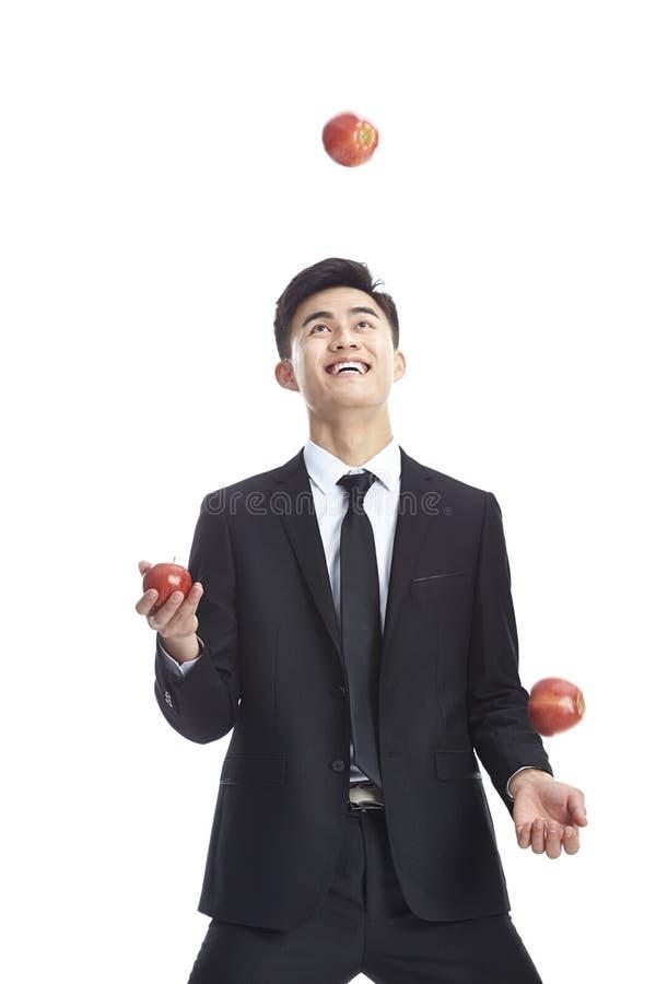 Asiatisk affärsman som jonglerar tre äpplen royaltyfria foton