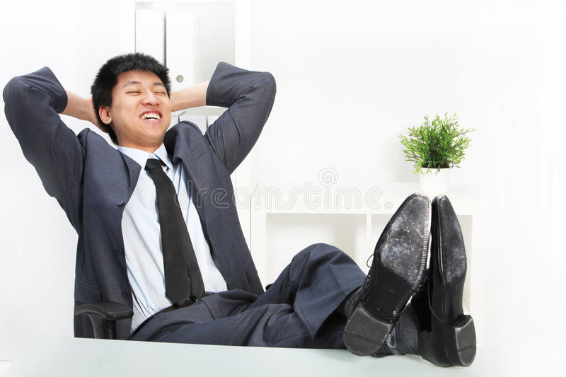 Asiatisk affärsman som kopplar av med hans fot upp royaltyfri foto