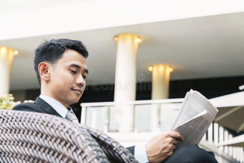 Asiatisk affärsman som läser en tidning royaltyfri foto
