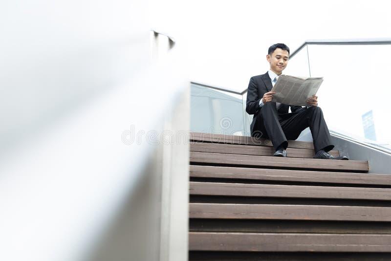 Asiatisk affärsman som läser en tidning fotografering för bildbyråer