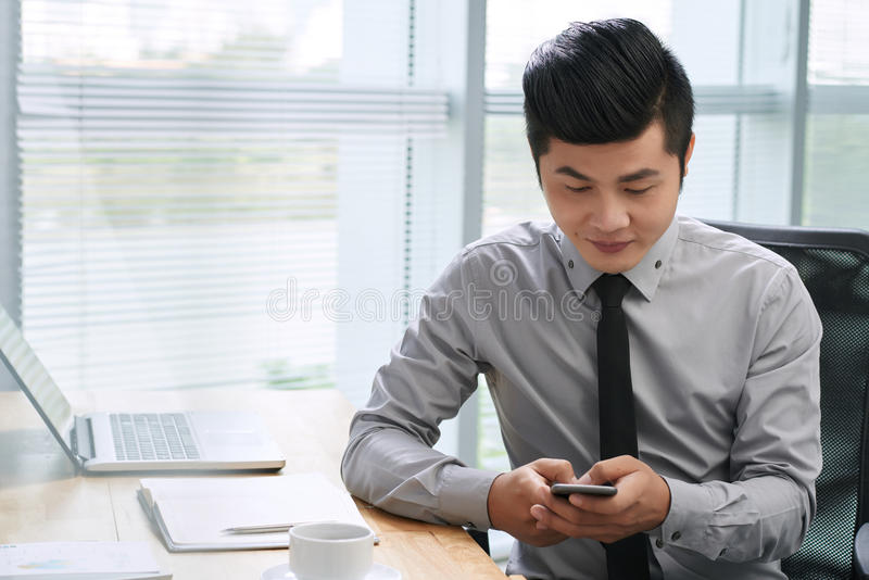 Asiatisk affärsman som smsar på smartphonen arkivfoto