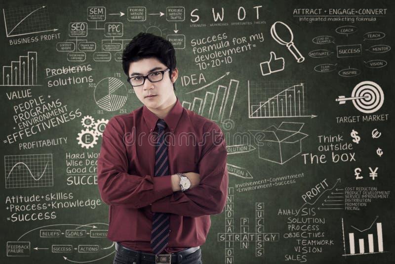 Asiatisk affärsman som står över framgångformel royaltyfri bild