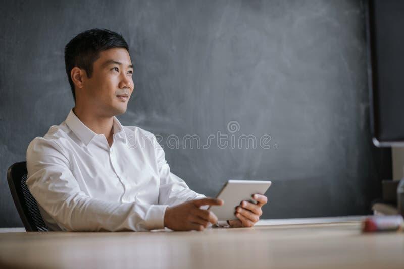 Asiatisk affärsman som tänker, medan arbeta på en minnestavla arkivfoto