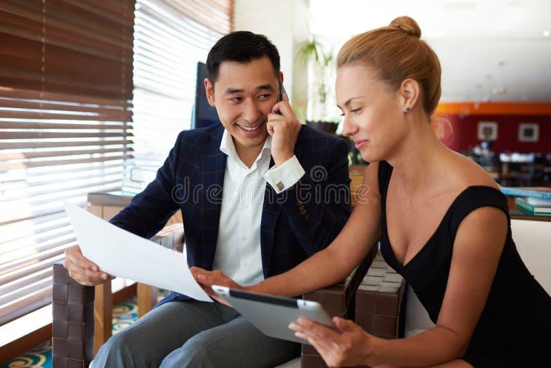 Asiatisk affärsman som talar på mobiltelefonen medan hans kvinnliga partner som använder den digitala minnestavlan arkivbild