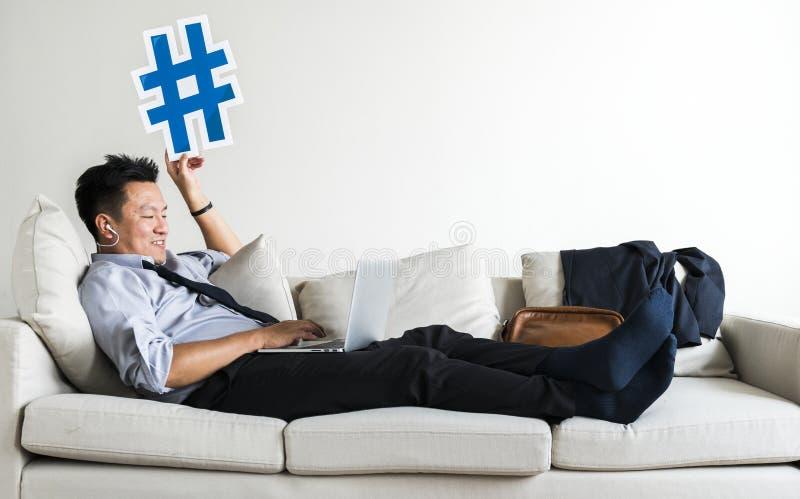 Asiatisk affärsman som tar avbrottet som lägger på soffan royaltyfri fotografi