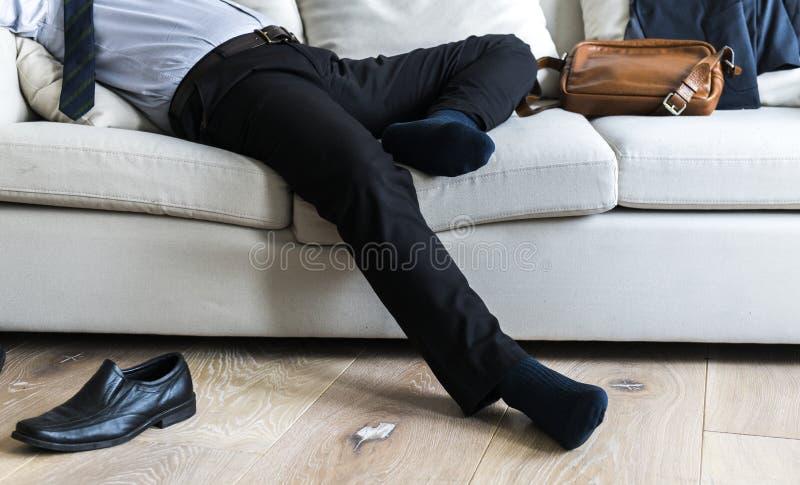 Asiatisk affärsman som tar avbrottet som lägger på soffan fotografering för bildbyråer