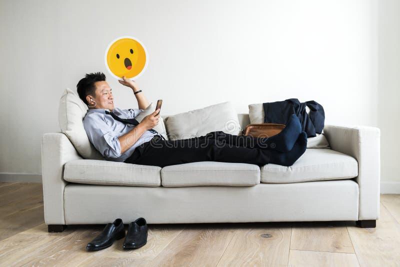 Asiatisk affärsman som tar avbrottet som lägger på soffan royaltyfria bilder