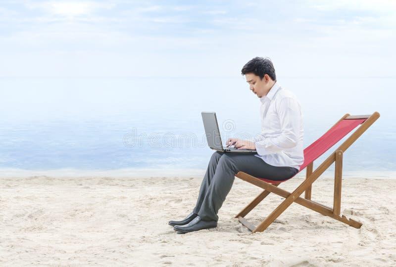 Asiatisk aff?rsman som arbetar med b?rbara datorn som sitter i strandstolen p? stranden arkivfoton