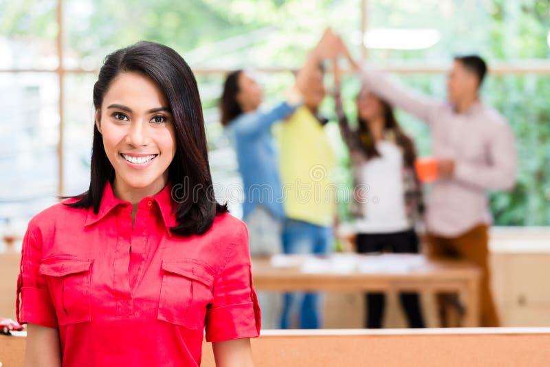 Asiatisk anställd som är lycklig att vara medlemmen av ett lyckat idérikt lag arkivbild