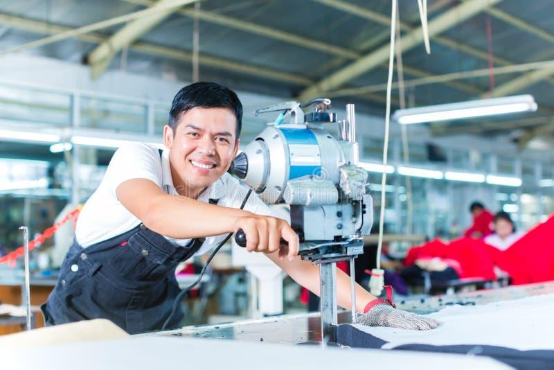 Asiatisk arbetare som använder en maskin i en fabrik arkivfoton