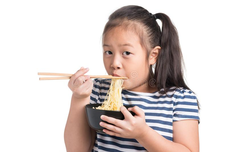 Asiatisk barnflickaålder 7 år som äter ögonblickliga nudlar på vit b arkivfoto