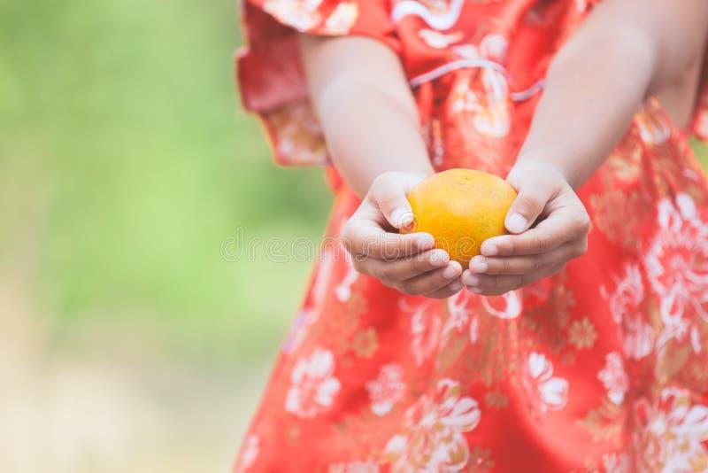 Asiatisk barnflicka i den traditionella klänningen för porslin som rymmer en apelsin royaltyfria foton