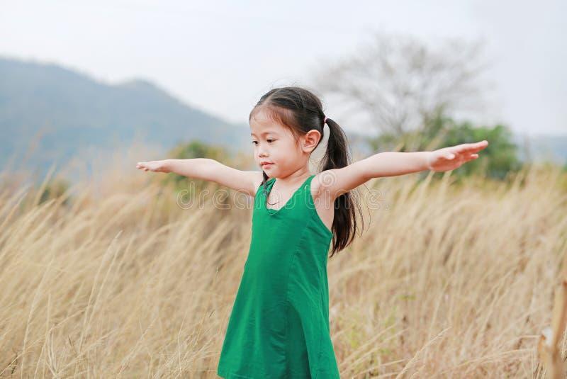 Asiatisk barnflicka med utsträckta armar i fältet för torkat gräs isolated rear view white arkivbilder