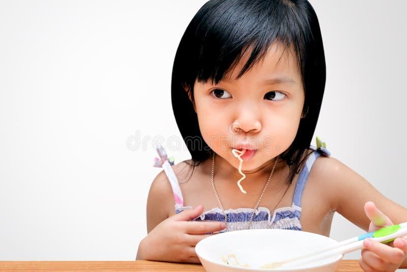 Asiatisk barnflicka som äter ögonblickliga nudlar royaltyfri bild