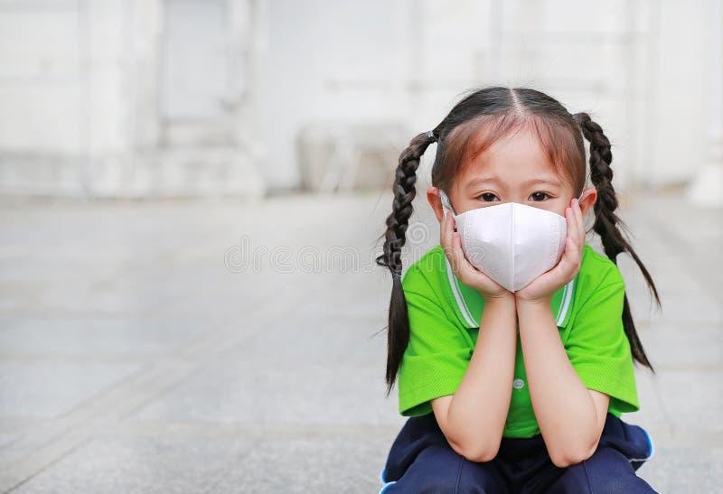 Asiatisk barnflicka som b?r en skyddsmaskering medan utanf?r till mot e.m. 2 luftf?rorening 5 med att peka upp i den Bangkok stad royaltyfria bilder