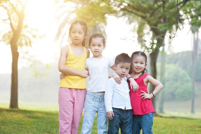 Asiatisk barngruppstående utomhus fotografering för bildbyråer