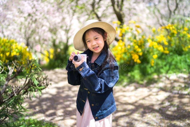 Asiatisk barninnehavkamera som tar fotoet på att resa tur under semester arkivfoto