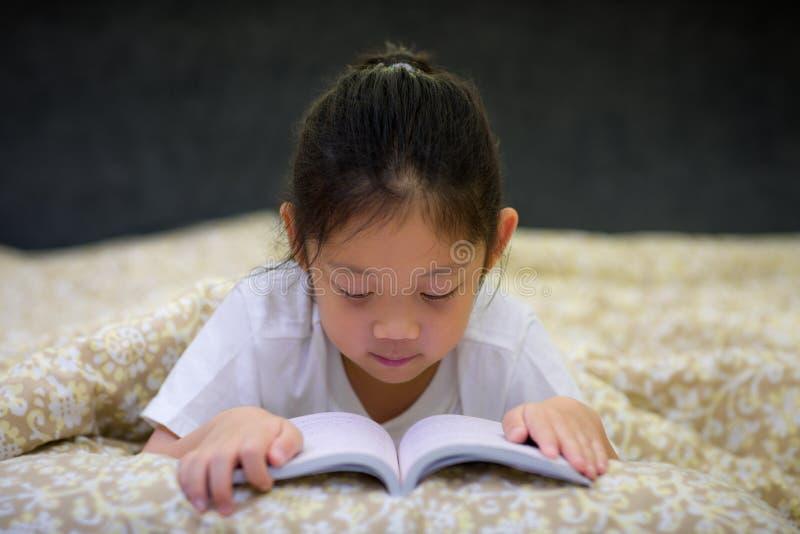 Asiatisk barnläsebok i säng fotografering för bildbyråer