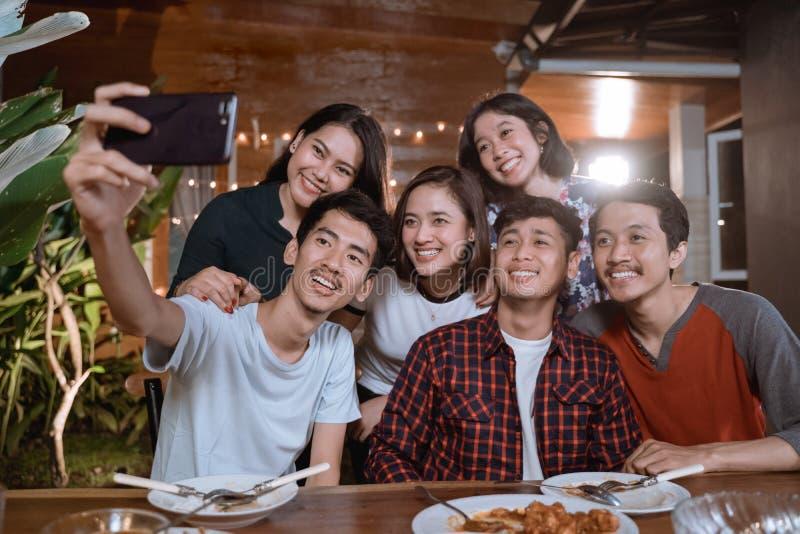 Asiatisk bestfriendgrupp att ta selfie med smartphonen, medan ha trädgårdpartiet fotografering för bildbyråer