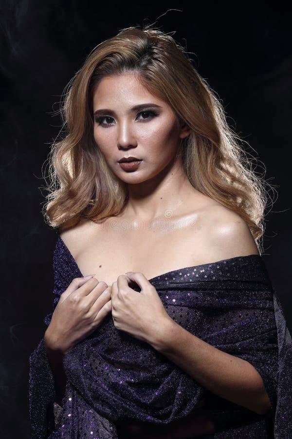 Asiatisk blond våghårkvinna, öppna skuldror för stående med purpl arkivbilder