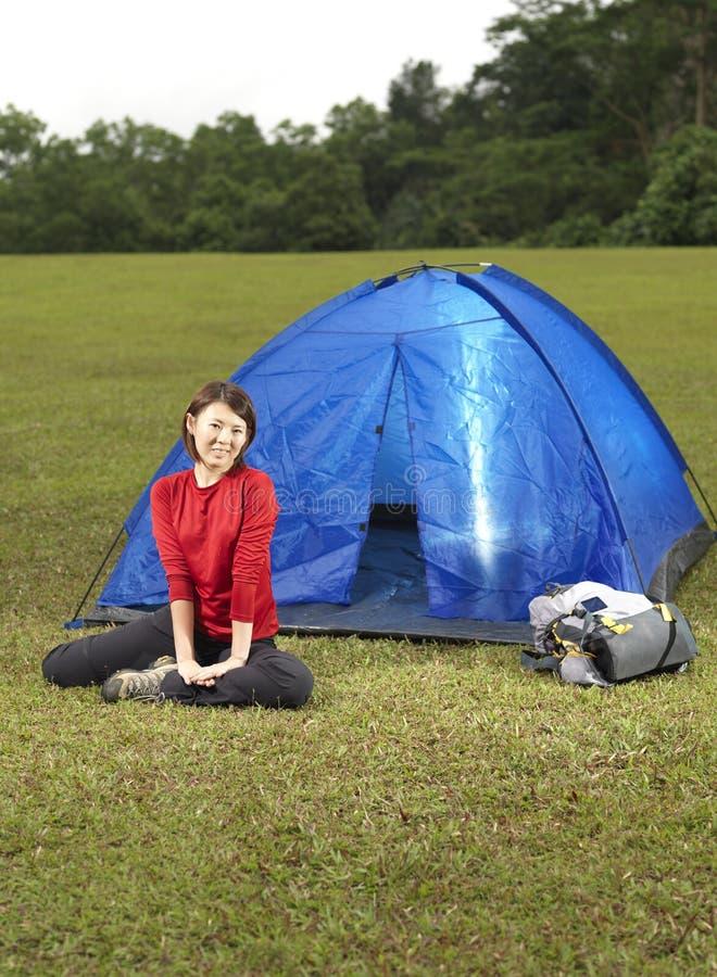 asiatisk camparekvinnlig henne sittande tent för yttersida royaltyfria bilder