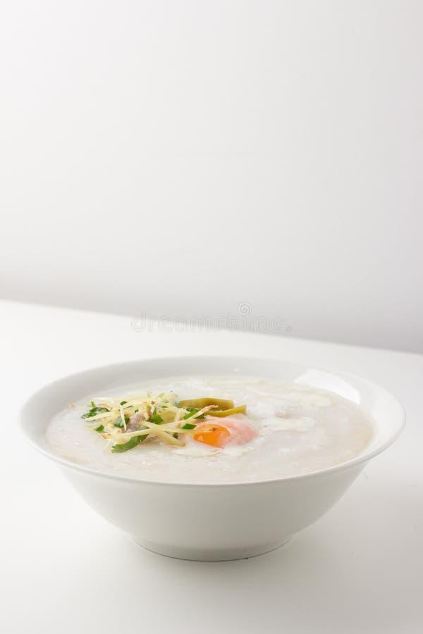 Asiatisk congee med det finhackade griskött och ägget i bunke arkivbilder