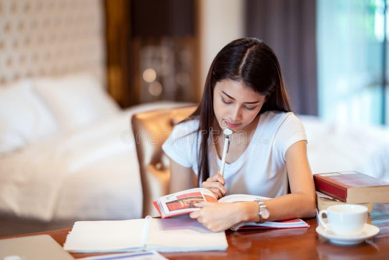 Asiatisk dam att göra hennes hem- arbete i hennes sängrum royaltyfri fotografi