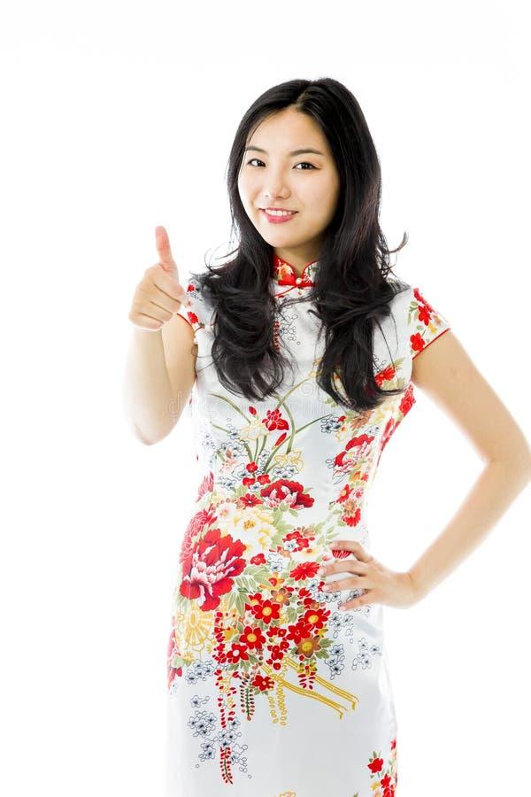 Asiatisk danande för den unga kvinnan tummar upp teckenanseende med handen på höft royaltyfria bilder