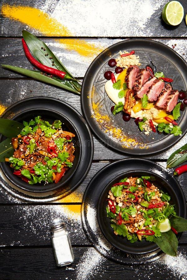 Asiatisk disk på en svart tabell Andbröst med persikan, nudlar med nötkött, blockthai med höna och räkor fotografering för bildbyråer