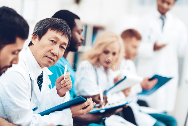 Asiatisk doktor Camera Staring During föreläsningen fotografering för bildbyråer