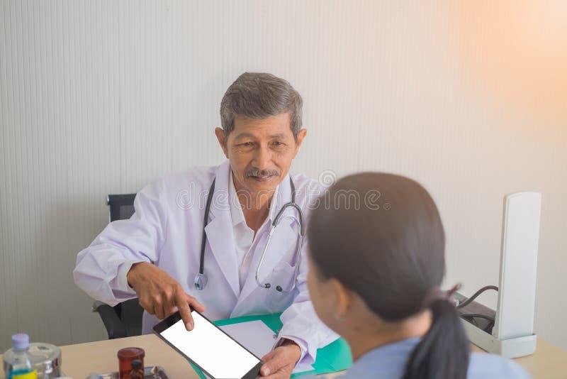 Asiatisk doktor för hög man som talar till den kvinnliga patienten i doktorskontor royaltyfri fotografi