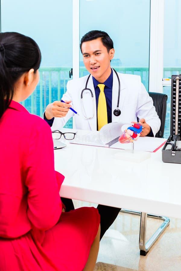 Asiatisk doktor med patienten i medicinsk kirurgi arkivbild