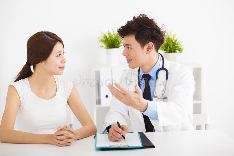 Asiatisk doktor som talar med den kvinnliga patienten fotografering för bildbyråer