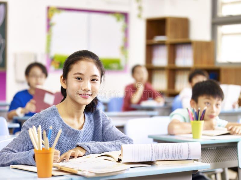Asiatisk elementär skolflicka i grupp arkivfoto