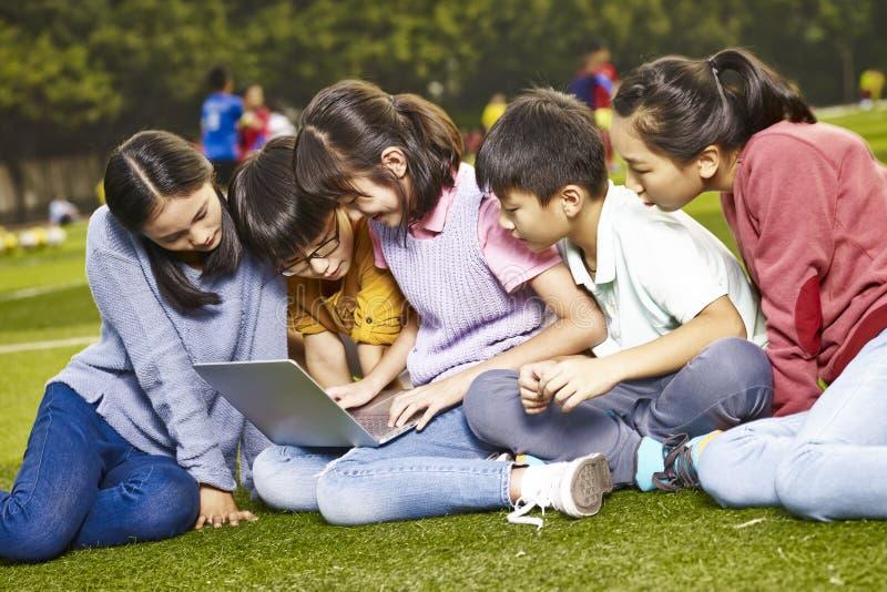 Asiatisk elev som utomhus använder en bärbar dator fotografering för bildbyråer